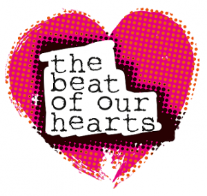 A pink heart overlaid with orange dots. In the centre, typewriter text reads 'the beat of our hearts'.