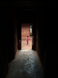 Dark hallway leading to a bright outdoor area, where a small child with pink clothes stands, facing the camera.