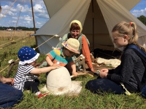 Young visitors learn to use an Iron Age quern